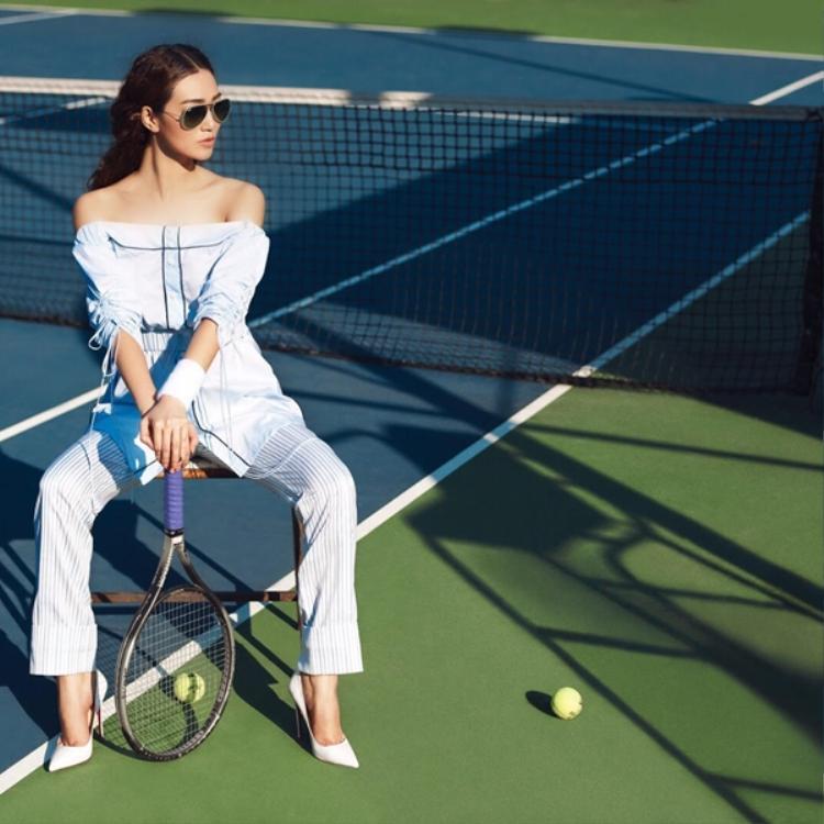 Cầm vợt tennis đầy khỏe khoắn trên sân tập, người đẹp diện những kiểu trang phục với thiết kế thanh lịch: áo trễ vai, chất liệu mỏng nhẹ và bay bổng