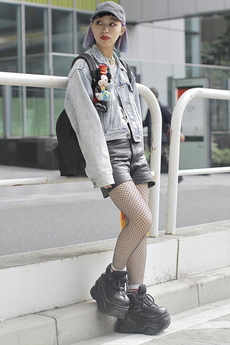 """Nếu bạn đã từng theo dõi streetstyle Tokyo Fashion Week 2016 thì có lẽ sẽ nhận ra cô gái với đôi giày ấn tượng này ngay thôi. Vẫn trung thành với tất lưới và giày đế bánh mì hầm hố, nhưng năm nay mái tóc tết đủ màu sắc đã được thay bằng tóc bob tím pastel khá """"high fashion"""""""