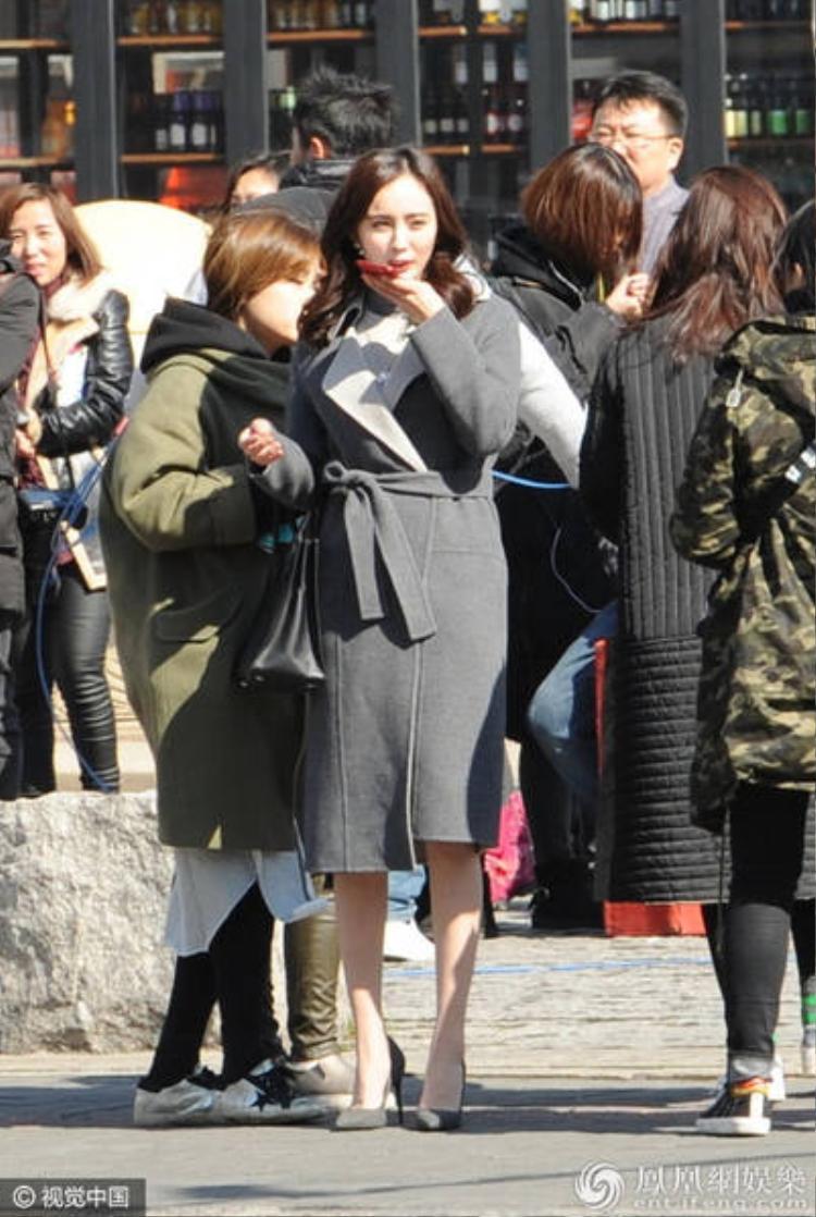 Nữ diễn viên thoải mái xuất hiện trên một con đường của thành phố Thượng Hải và có vẻ đang gọi điện cho ai đó.