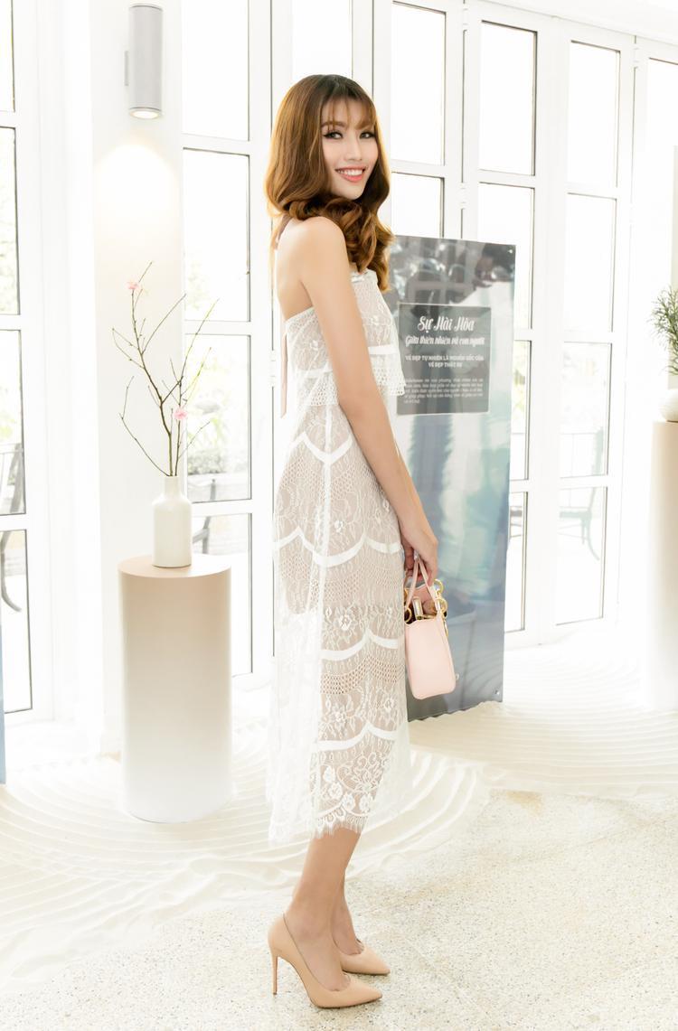 Chọn bộ đầm quây chất liệu ren trắng mỏng manh, Quỳnh Châu khoe được làn da trắng ngần và vóc dáng thanh thoát, tôn chiều cao 1m74 chuẩn mực. Cô trang điểm tông cam đất với đôi mắt sắc sảo ấn tượng như con gái phương Tây.