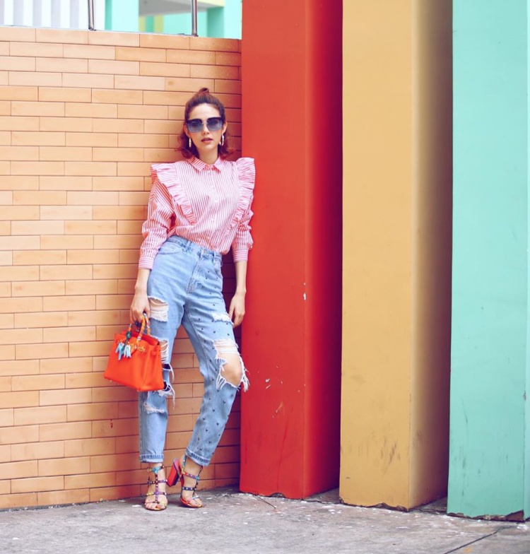 Sơ mi sọc bèo nhún, túi xách màu cam, jeans rách và sandals color block của Minh Hằng tưởng như không liên quan nhưng khi kết hợp lại với nhau lại tạo nên 1 tổng thể đầy hòa hợp. Tất nhiên chúng ta không thể bỏ lỡ chiếc kính gọng vuông cực bắt mắt của mỹ nhân.