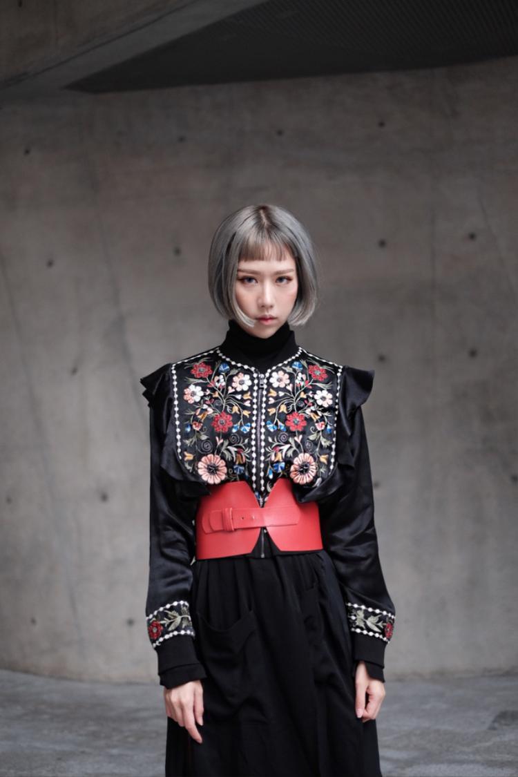 """Lấy tông màu đen làm chủ đạo. chiếc áo được thêu họa tiết hoa cầu kì đi kèm với thắt lưng da bản to màu đỏ vô cùng bắt mắt. Mái tóc """"maruko"""" xám cũng là một nét thay đổi mới với diện mạo của Min."""