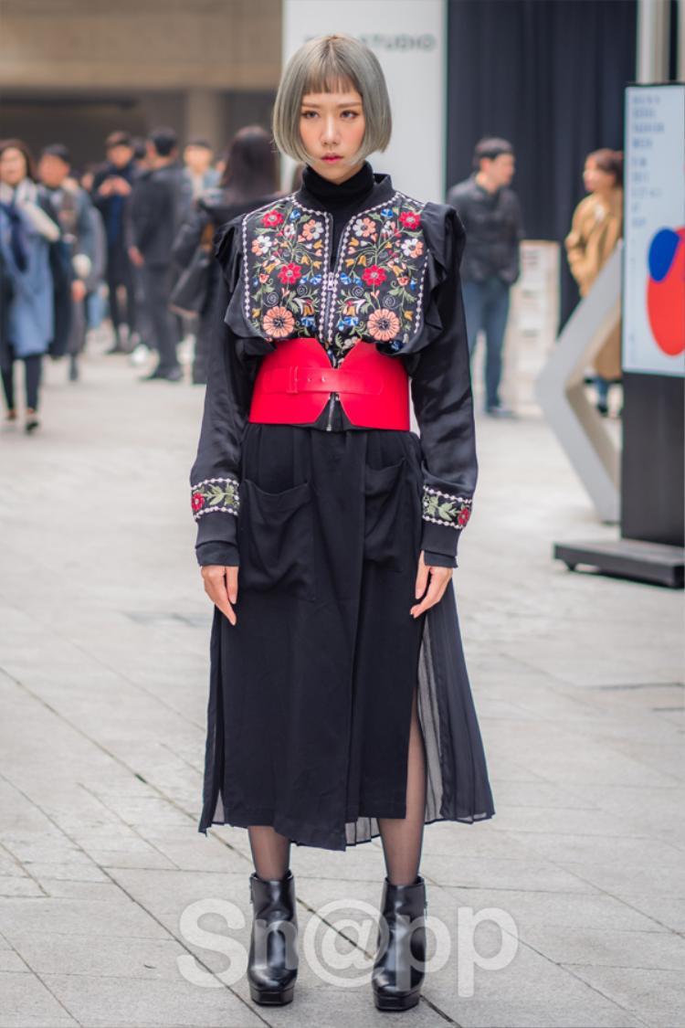 Min chọn một chiếc váy đen được tạo điểm nhấn bằng đai thắt màu đỏ, liên kết với những họa tiết được thêu tỉ mỉ phần thân áo.
