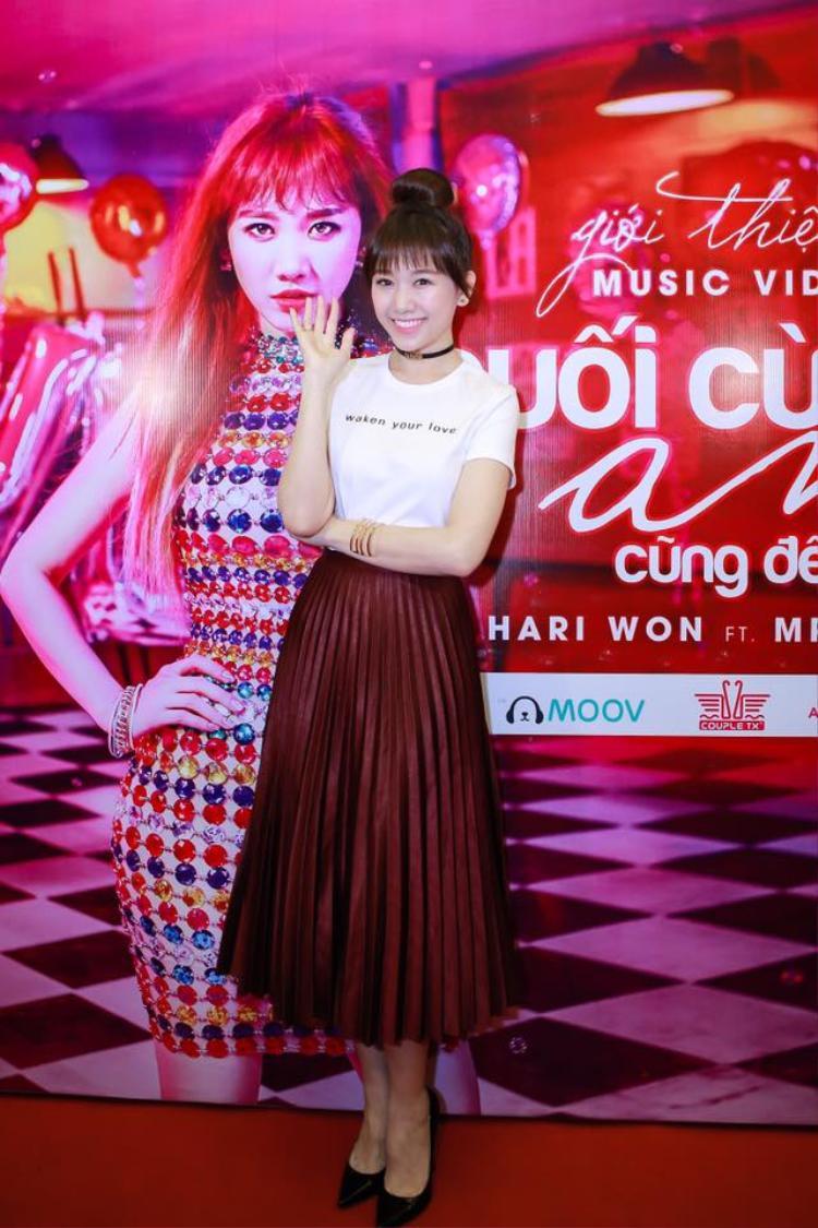 Chân váy xếp pli màu đỏ rượu mix cùng áo thun trắng đơn giản và vòng choker, lẽ ra đây thường là outfit để các nàng trưng diện ngoài phố nhưng Hari Won mạnh dạn diện chúng để xuất hiện trong sự kiện ra mắt MV trước đông đảo các kênh truyền thông.