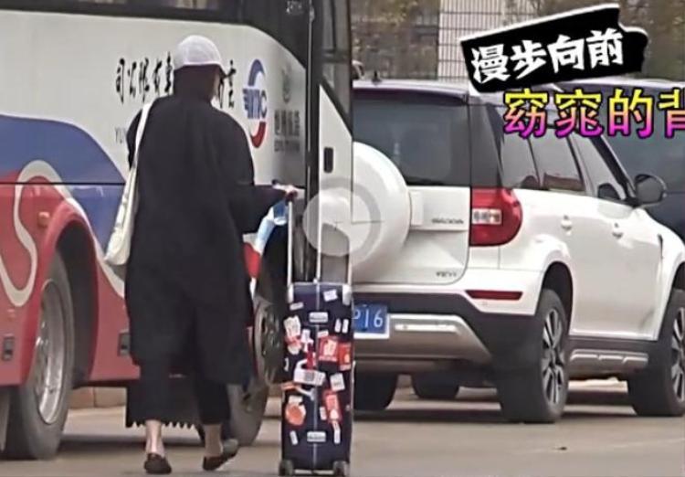 Cô gái bí ẩn với áo khoác đen đẩy vali đi về phía chiếc xe màu trắng của Hoàng Hiên.