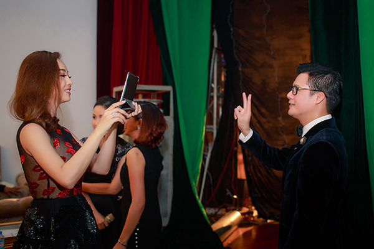 Jennifer Phạm tranh thủ chụp hình cho Quang Dũng phía trong hậu trường sự kiện.