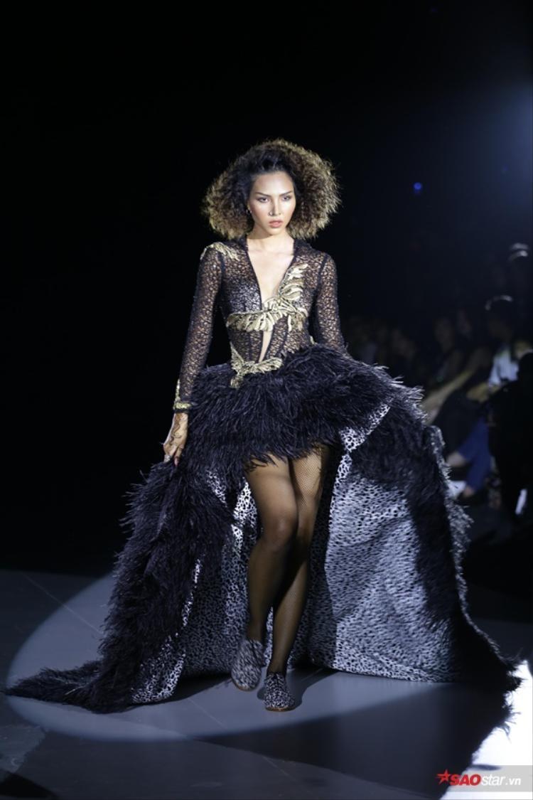 Minh Triệu mở màn đầy mạnh mẽ và quyền lực với thiết kế váy độc đáo được trên nền họa tiết da beo và lông vũ mềm mại.