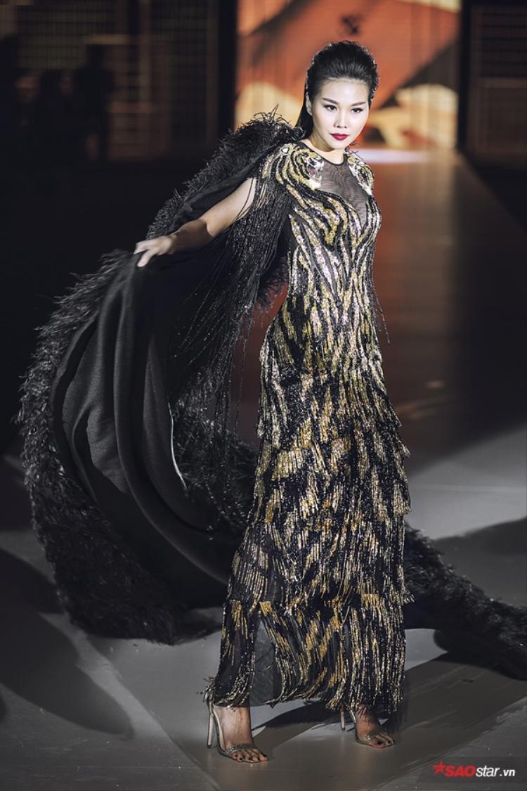 Vạt khoác này sử dụng đến 325m lông vũ và nặng 15kg. Nó không chỉ là mảnh ghép hoàn hảo nâng tầm tinh thần của tổng thể trang phục mà còn sự thử thách lớn cho người mẫu trình diễn.