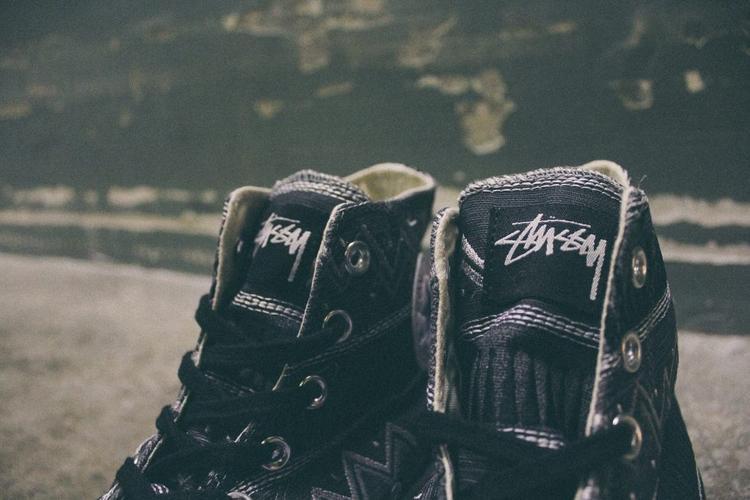 """""""Thương hiệu tuổi thơ"""" mong muốn mang đến họa tiết thổ dân độc quyền Tom Tom như đường zig zag, gợn sóng (wavy) và các chấm nhỏ một cách chân thật. Dĩ nhiên chúng hoàn toàn được hiện đại hóa để tạo sự mới mẻ và phù hợp với phong cách trẻ thời nay. Với 2 tông màu đậm nhạt, phần gót giày được thêu từ chất liệu woven bằng chỉ đen/trắng (monochrome). Logo Stüssy xuất hiện trên lưỡi gà, bên trong lót giày và dưới đế giày trong suốt (translucent)."""