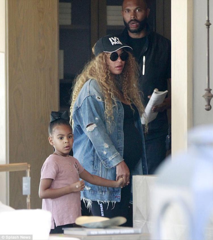 Ngôi sao nhạc pop giản dị nắm tay con gái yêu cùng đi mua sắm dưới sự hộ tống của hai vệ sĩ nhà mình.