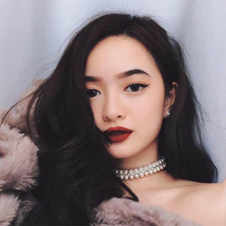 """Mặc dù sử dụng màu son đỏ rượu già dặn, nhưng cô nàng hot girl """"em chưa 18"""" đã kéo lại được vài tuổi khi trang điểm nhẹ nhàng cho đôi mắt và chỉ nhấn nhá bằng đường eyeliner."""
