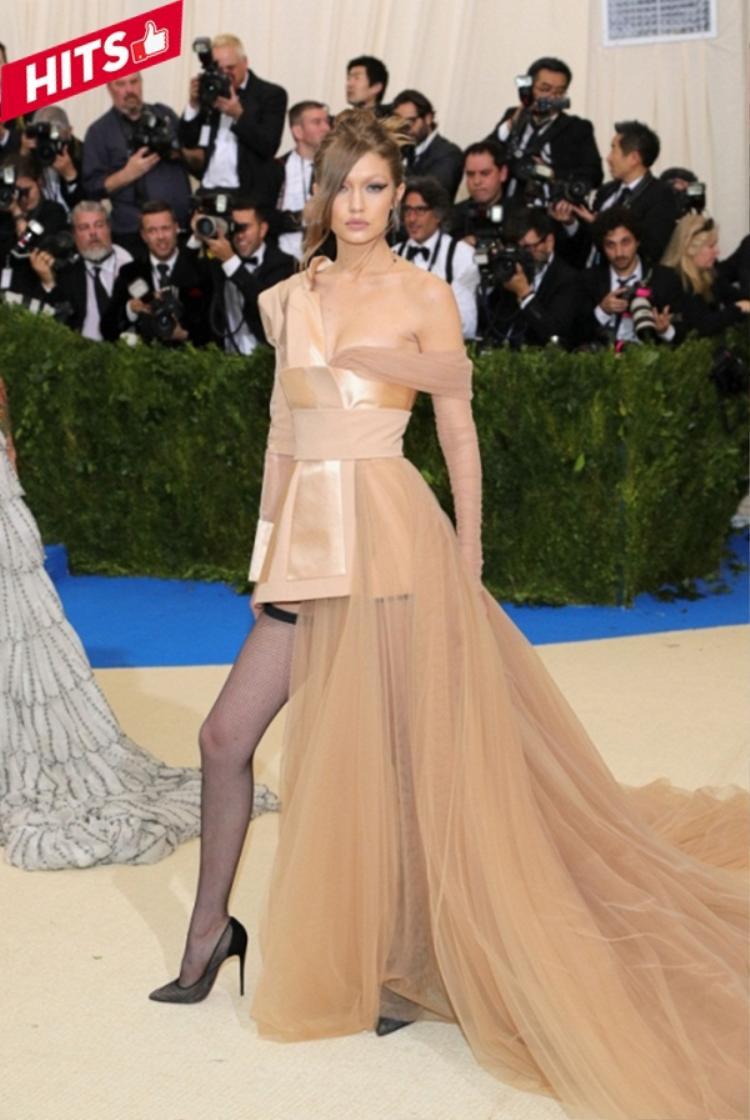 Nàng siêu mẫu instagram Gigi Hadid vô cùng ấn tượng với mẫu váy bất đối xứng gam màu beige độc đáo khoe trọn vẻ đẹp hình thể từ thương hiệu Tommy Hilfiger. Không chỉ thể hiện vẻ sexy thông qua trang phục mà ngay kiểu tóc và lối make-up cũng nói lên được điều đó.