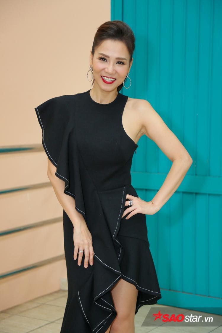 """Không còn chuộng phong cách """"nữ quyền"""" như tuần trước, HLV Thu Minh trở lại với chiếc váy đen xẻ đùi gợi cảm, thanh lịch."""