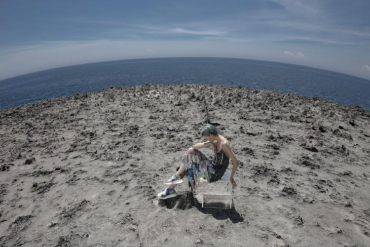 """hững góc máy rộng làm nổi bật thêm sự chơi vơi của bản thể """"Em Hoa"""" giữa vùng đất đá khô cằn và mặt biển xanh thẫm mê hoặc."""
