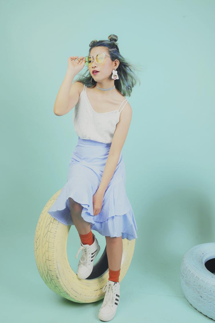 Mái tóc nhuộm xanh nổi bật kết hợp cùng trang phục và phụ kiện năng động tạo cho Nga Helen một vẻ ngoài tươi mới và hiện đại.
