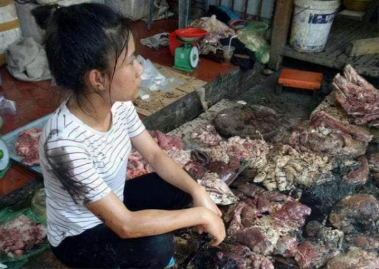Hình ảnh người phụ nữ bán thịt lợn bị đổ chất thải.