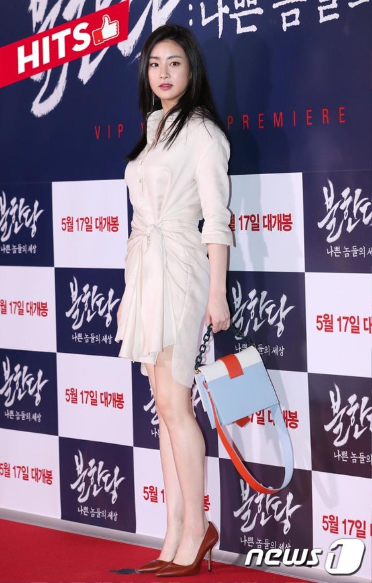 """Nữ diễn viên Kang Sora khoe """"cặp đùi vàng"""" trong thiết kế váy sơ mi chít eo duyên dáng. Chiếc túi xách màu xanh cam như tạo điểm nhấn giúp cả diện mạo thanh lịch của cô được tôn lên một cách hoàn mỹ nhất."""