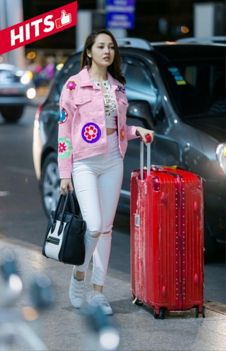 """Nữ ca sĩ Bảo Anh khoe thời trang sân bay sành điệu với túi hiệu Celine Luggage mix cùng cây trắng và không quên tạo điểm nhấn bởi chiếc áo khoác denim màu """"hường"""" nổi bật."""