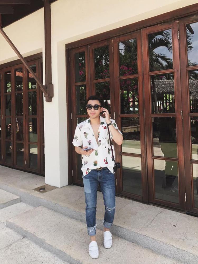 Nhưng họa tiết hoa lá mùa hè đâu chỉ dành riêng cho phái đẹp? Bằng chứng là stylist Hoàng Ku vẫn xuất hiện vô cùng thời trang và khỏe khoắn với mẫu áo sơmi trắng điểm xuyến đầy các hình ảnh tượng trưng cho mùa hè cùng jeans rách phóng khoáng.