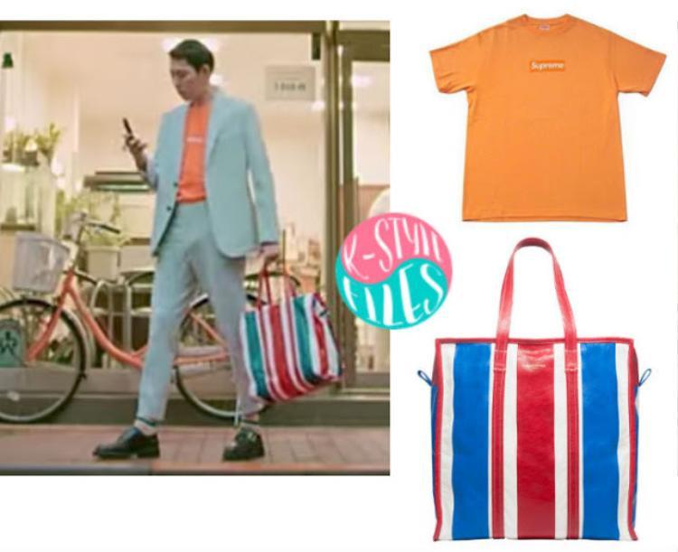 Nhân vật phụ tiếp theo hé mở với set đồ bao gồm áo T-shirt Supreme màu cam cà rốt và chiếc túi Balenciaga như túi đi chợ.