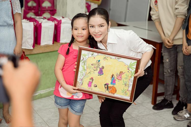 Lý Nhã Kỳ càng hạnh phúc hơn khi nhận được món quà là bức tranh được chính các bé mồ côi tại Trung tâm Nuôi dưỡng Bảo trợ Trẻ em Tam Bình thực hiện.
