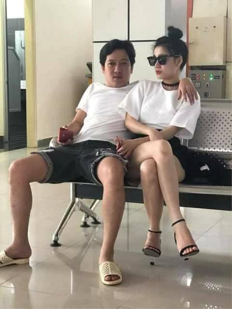 """Hình ảnh tình tứ của một trong những cặp đôi hot nhất nhì làng giải trí Việt tại sân bay. Nam nghệ sĩ hài luôn trung thành với phong cách giản dị đặc trưng - quần lửng, áo phông và đôi dép tổ ong """"thương hiệu""""."""