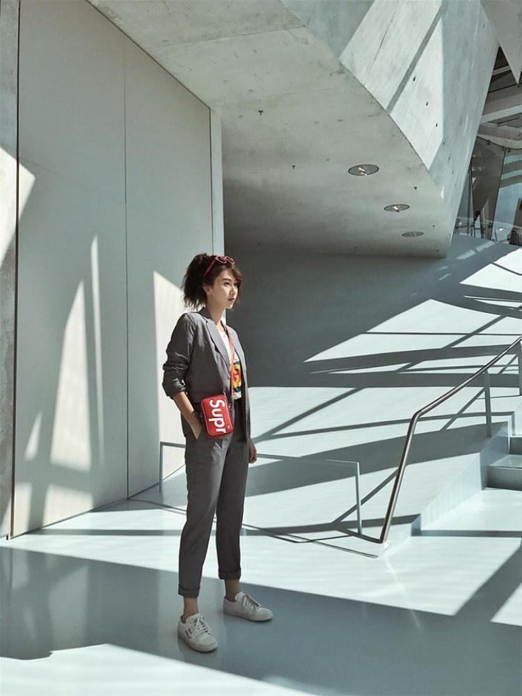 """Quỳnh Anh Shyn đang ngày càng """"xa hoa hóa"""" phong cách thời trang của mình khi liên tục tậu các món đồ hiệu. Trong hình, cô nàng diện áo thun của nhà mốt Gucci, nguyên cây suit màu ghi xám của Candeblanc, giày Yves Saint Laurent và túi đeo chéo của Supreme."""