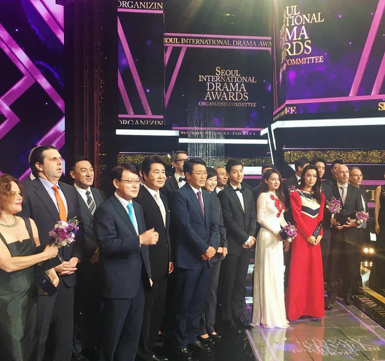 """Trong tà áo dài Việt Nam, Nhã Phương tươi tắn đứng cùng ngôi sao """"Hậu duệ mặt trời"""" Song Joong Ki tại lễ trao giảiSeoul International Drama Awards."""