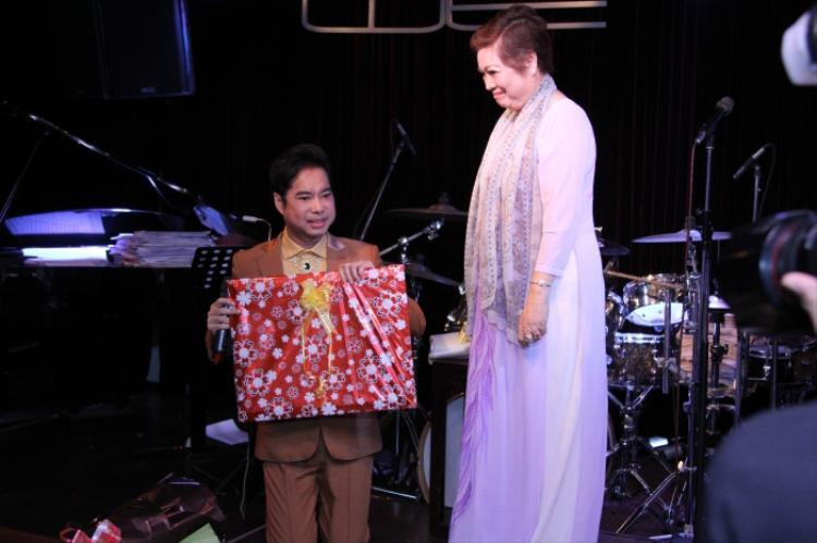 Ngọc Sơn quỳ gối trước mẹ trên sân khấu.