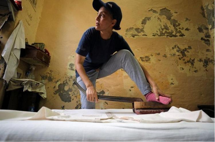 Ebtesam Mohamed đang dùng chân để ủi quần áo.