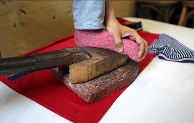 Miếng gỗ đặt giữa chân và miếng sắt để bảo vệ chân khỏi sức nóng.