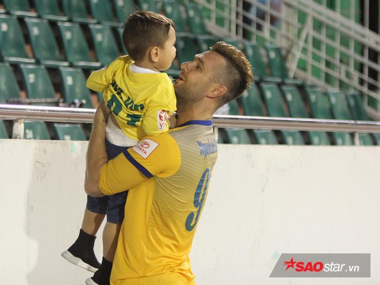 Trung vệ điển trai Nguyễn Van Bakel chơi đùa với cậu con trai giải buồn sau thất bại.
