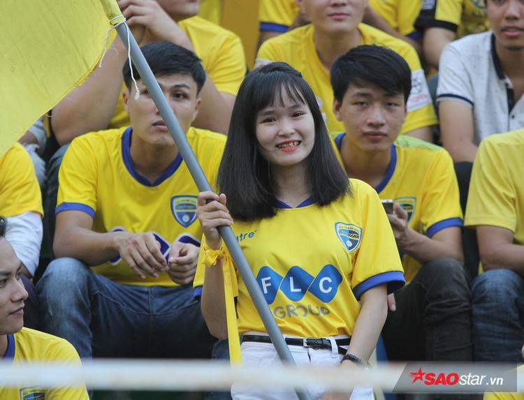 Fan nữ cầm cờ cổ vũ cho đội nhà.