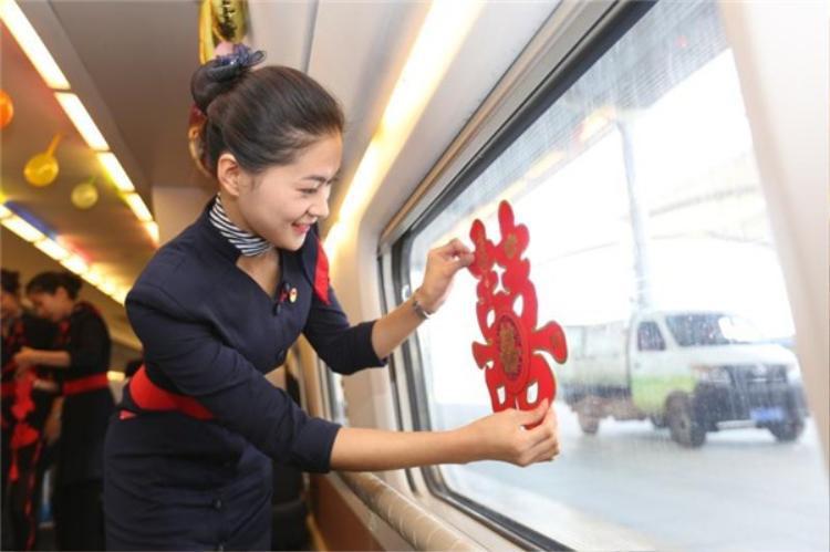 Một nhân viên đường sắt đang trang trí cửa sổ xe lửa cho cô dâu, chú rể.
