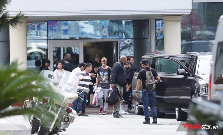 Andrew Taggart (quần xám, giày đỏ) cầm hành lý bước ra siêu xe đã được Phillip Nguyễn bố trí chờ sẵn.