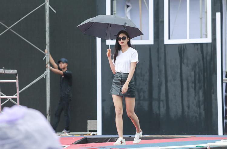 Bất chấp mưa gió, Mâu Thủy vẫn giữ được phong thái sang chảnh. Cô diện áo thun trắng, váy da đen kết hợp sneakers sành điệu lên sân khấu tập dượt.