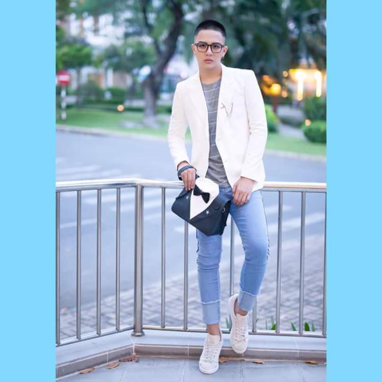"""Trong khi đó, Duy Khánh tạo nên hình ảnh """"Soái ca"""" với Vest trắng, layer áo thun cùng quần skinny jean sáng màu, điểm nhấn là chiếc túi cầm tay hình dạng áo veat độc đáo."""