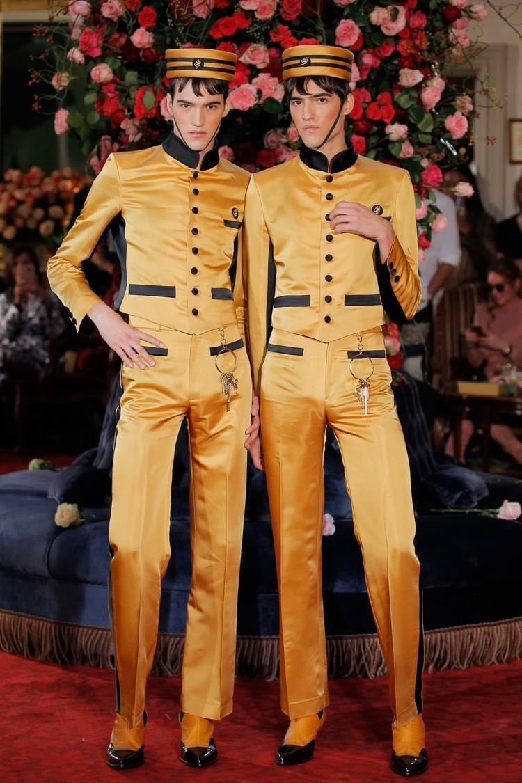 Mở đầu show diễn là hình ảnh hai lễ tân tại khách sạn trong trang phục suit mang đậm tính cổ điển với kiểu dáng ôm sát cùng chất liệu satin. Ngoài ra, điểm nhấn chính phục thuộc vào thần thái và layout make up, kèm theo sự uyển chuyển của cặp người mẫu nam trong đôi giày cao gót.