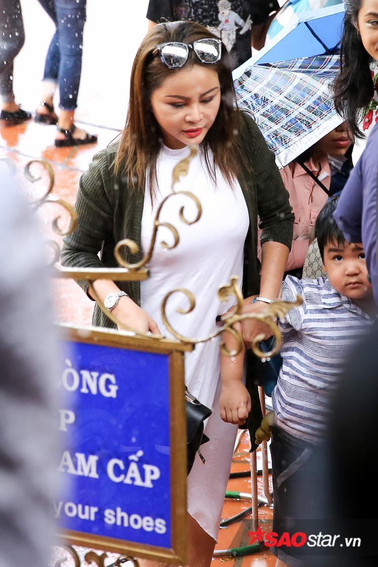 Nữ diễn viên hài Lê Giang đội mưa vào dâng hương.