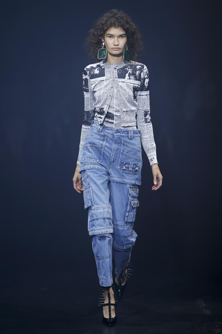 Bộ trang phục là sự kết hợp tinh tế giữa chiếc quần túi hộp lưng cao từ chất liệu jean đặc trưng cùng với chiếc áo in họa tiết một trang báo với kiểu dáng độc đáo. Điểm nhấn là đôi hoa tai đá xanh to bản.