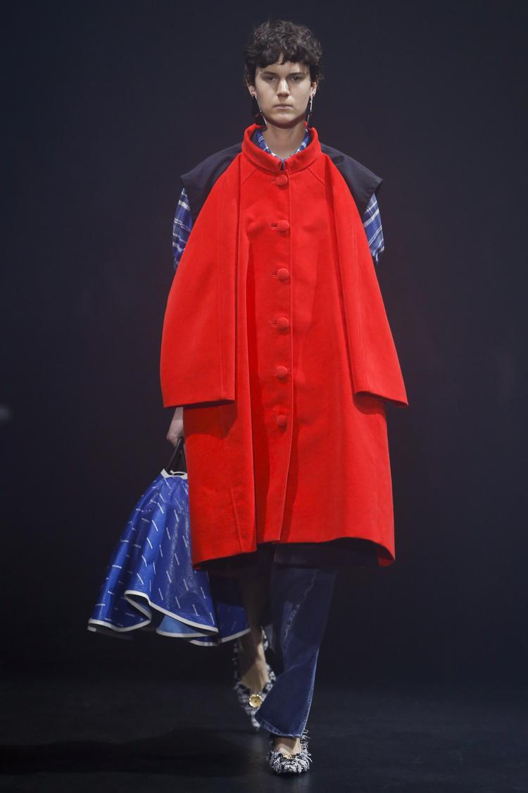 Sự phá cách trong thiết kế của thương hiệu Balenciaga được mô tả khá rõ nét. Áo măng tô đỏ được đính trên chiếc áo sơ mi caro form rộng.
