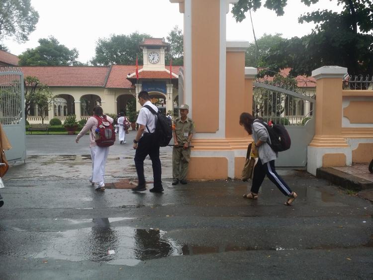 Nhiều bạn học sinh cúi chào bác bảo vệ từ xa.