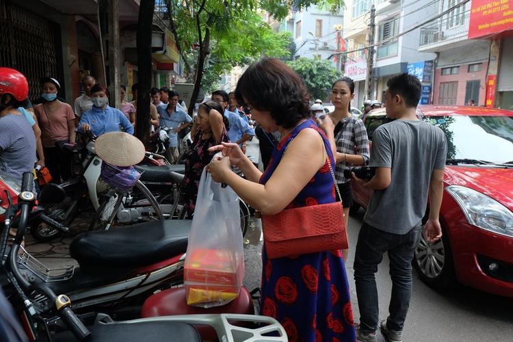 Cô Kim Tuyến vui vẻ khi mua được hai hộp bánh sau khi chờ đợi suốt 1 giờ đồng hồ.