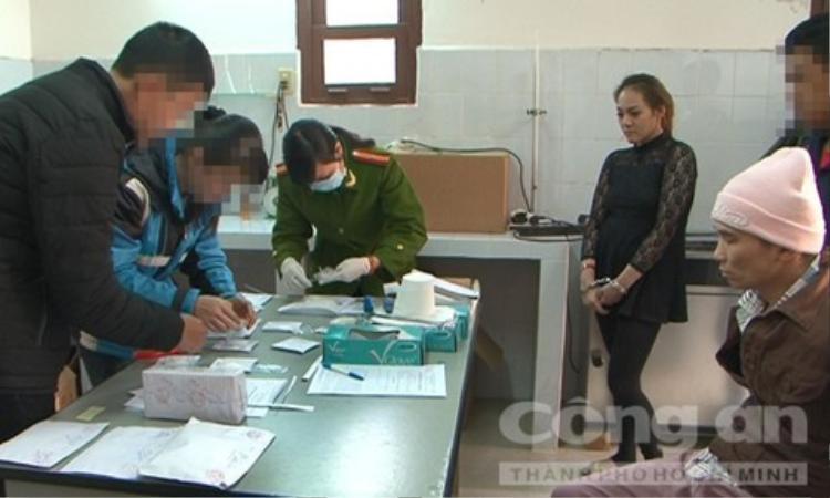 Trang và Lân (đội mũ len) chứng kiến việc kiểm kê tang vật vụ án.