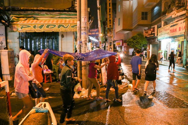Khi mưa tạnh, nhiều người phải che áo mưa đi chơi.