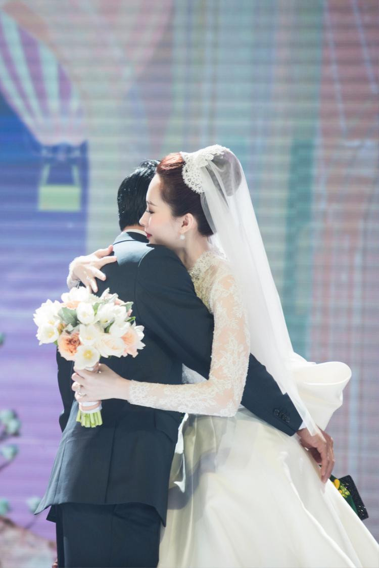 Thiết kế thứ hai được nhà thiết kế thân thiết Lê Thanh Hoà dành tặng cho Đặng Thu Thảo. Khác với vẻ nữ tính của bộ váy đầu tiên, váy cưới của tiệc chính mang hơi hướng cổ điển với phần tay áo ren dài. Khoăn voan cài tóc cô dâu cũng theo chủ đạo màu trắng.