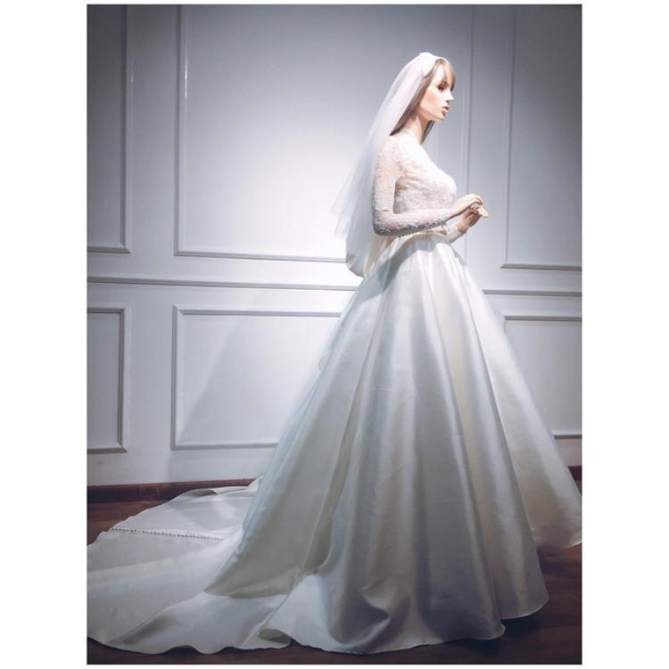 Thiết kế với phần voan nhẹ nhàng phủ kín từ cổ xuống cánh tay khá kín đáo nhưng vẫn giúp cô dâu khoe được vẻ đẹp hình thể.