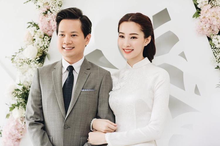 """Bộ vest xám trong lễ đính hôn cùng caravat lụa vô cùng tinh tế của Trung Tín, một phần vừa tôn lên vẻ đẹp của chính mình, phần lại rất """"ăn nhập"""" với chiếc áo dài trắng của NTK Thuận Việt."""