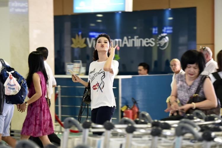Huyền My chu môi xì tin ở sân bay.