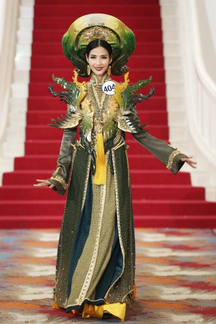 Hoàng Thùy đầy uy quyền với bộ quốc phục mang tên phượng hoàng, có gam màu xanh chuyển sắc, cùng các chi tiết đính kết cầu kì. Thiết kế có phần áo khá dài, mấn nặng nề không làm khó những bước di chuyển của Hoàng Thuỳ.